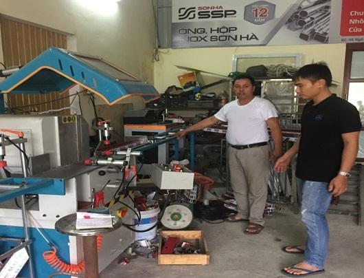 Anh Đại (áo trắng) hướng dẫn người lao động sử dụng hệ thống máy tiên tiến ứng dụng vào sản xuất tại xưởng
